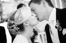 Ein Hochzeitspaar nach der Trauung gibt sich, unbemerkt von den übrigen Gästen beim Sektempfang ein flüchtiger Kuss