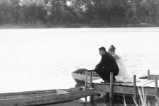 Nah Achern nimmt sich die Braut paar eine Auszeit vom Hochzeitsfest und verweilt am Ende einer Steg und betrachtet das Spiel von Wasser und Licht, während sie von eine romantische Gegenlicht von der abendliche Sonne umwaschen werden.